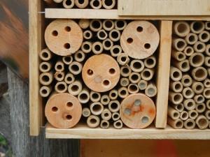 Image of bamboo tubes sealed with mud that looks like masonry.