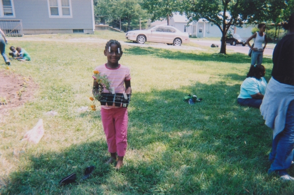 young girl carrying flowers to plant
