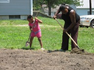 a child and adult prepare a garden bed with hoes