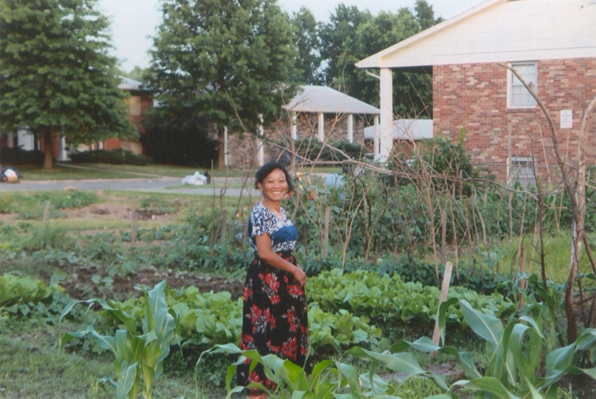 a gardener from southeast Asia stands in her summer garden plot
