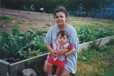 a Latino gardener kneels in front of her garden bed with her young son
