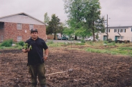 a Latino gardener stands in the newly tilled spring garden holding a transplant