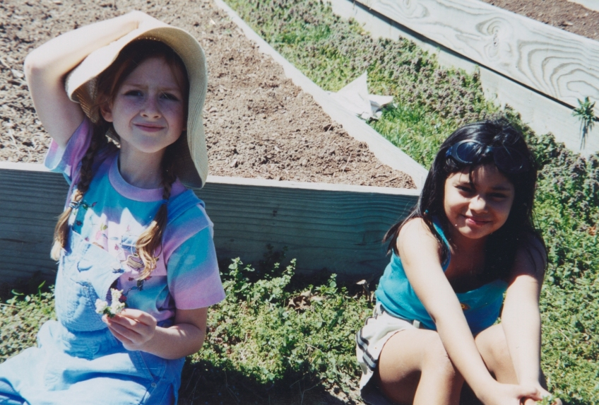2 young girls sit in front of a raised bed ready to plant