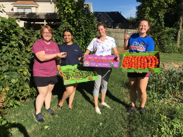 Columbia College students showing garden produce just picked for donation