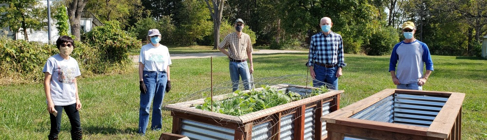 Interfaith Garden board members and Matt Knowlton pose at the garden with raised planters