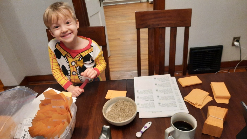 A young boy smiles at a table full of bulk seeds, labels and seed envelopes.